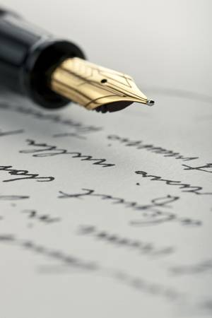 fountain pen writing: Gold pen with hand written letter. Focus on end tip of fountain pen.