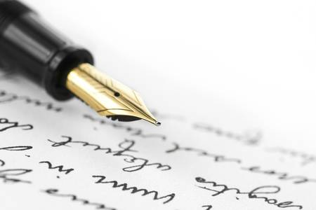 Gold pen with hand written letter. Focus on end tip of fountain pen.