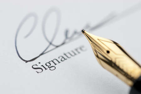 Gold pen with signature and document in background. Focus on tip of fountain pen nib. Archivio Fotografico