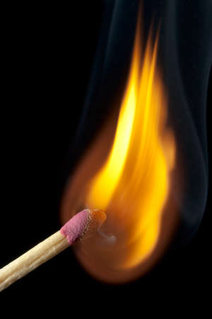 Macro view of matchstick on fire and burning on black background
