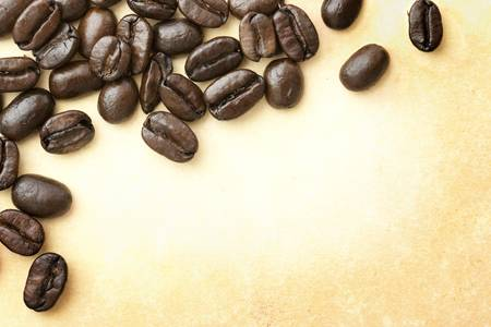 Fresh roasted coffee beans background on vintage ages paper. Focus on coffee beans. 스톡 콘텐츠