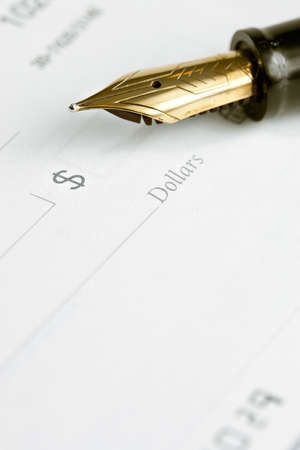 blank check: Fountain pen on blank check. Focus on tip of pen and dollar sign symbol