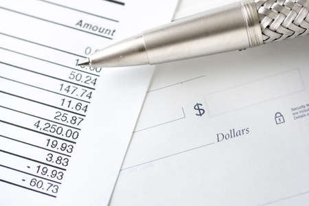 blank check: Pen on blank check with credit card balance. Focus on pen tip and dollar sign symbol Stock Photo
