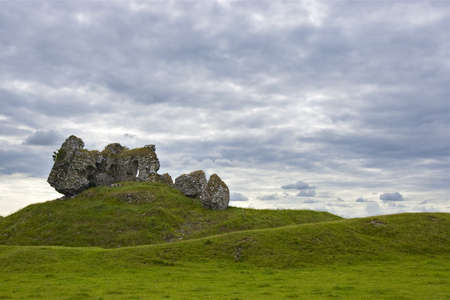 Old Castle in Republic of Ireland agains grassy hills and cloud filled sky