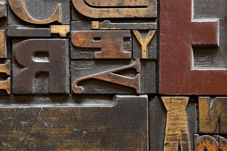 wood texture: Old printing press letters arranged randomly across. Focus across entire surface. Stock Photo
