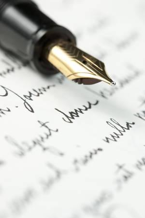 Selective focus on gold pen over hand written letter. Focus on tip of pen nib. Standard-Bild