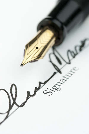 Gold fountain pen over obscured signature on document. Focus on tip of pen nib.