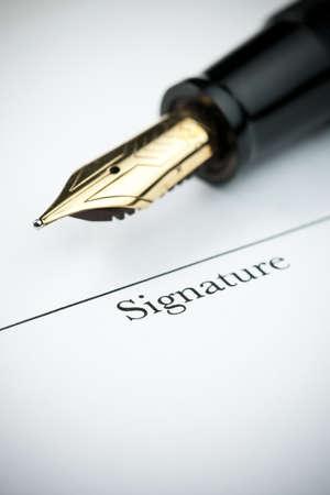 nib: Pen resting above signature line of document. Focus on tip of pen nib.