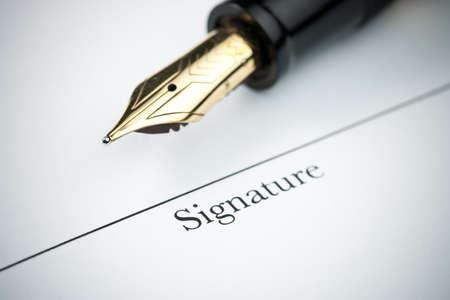 autograph: Pen resting above signature line of document. Focus on tip of pen nib.