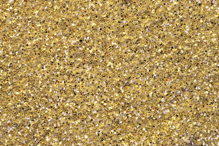 Top view of gold yellow glitter background. Focus across entire surface.