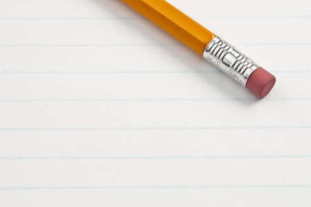 Eraser pencil end on note pad lined paper. Focus on eraser end of pencil.
