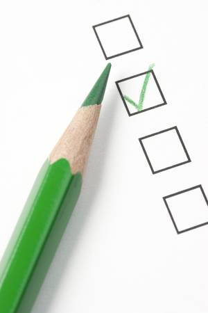 Green check box on survey box with green pencil. Focus on tip of pencil Imagens