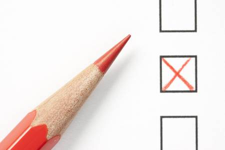 Red pencil next to survey check boxes and red x symbol. Focus on tip of pencil.