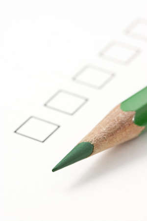 Check box on survey with green pencil. Focus on tip of pencil
