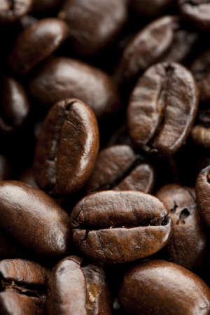 Coffee beans background with selective focus on one bean. Imagens