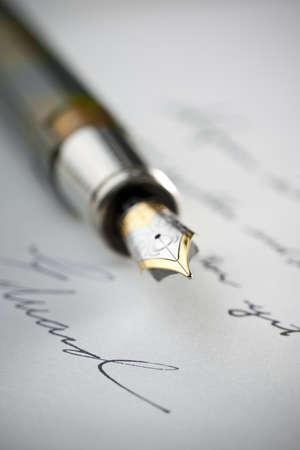 ペン先の先端に選択的な焦点と手紙を書いたの手にゴールド万年筆。