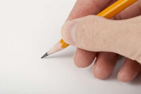 右手は鉛筆で書きます。鉛筆の先端に焦点を当てます。 写真素材