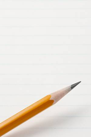 Pencil across lined note pad paper. Focus on tip of pencil. Archivio Fotografico
