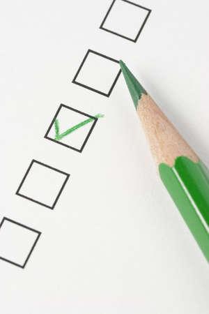緑色鉛筆とチェック マークを調査します。鉛筆の先端に焦点を当てます。