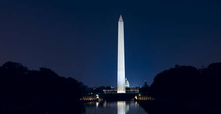Washington Monument with US Capitol. Late night iew with glow of city lights.