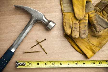 ハンマー、釘、測定テープ、ウッドの背景に建設手袋。夜表面の間で焦点を当てます。