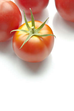 Ripe red tomatoes on white background along top of frame. Copy space beneath Archivio Fotografico