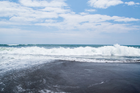 ocean waves: lovely bay with black sand and big ocean waves in Indian Ocean