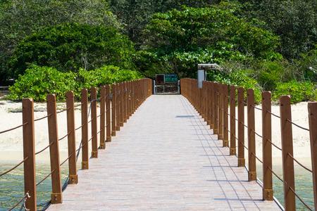 orenge: Wooden railings on the pier on the beach Stock Photo