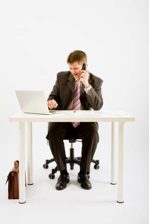 Young businessman working with phone and laptop computer Stock Photo - 5474398