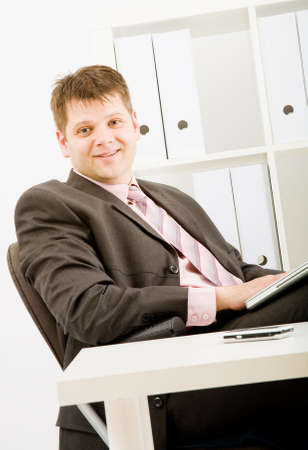 Young businessman working with phone and laptop computer photo