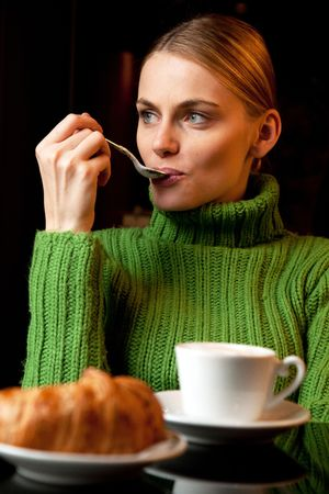 young woman with a spoon in her mouth making breakfast with a cup of cappuccino and croissant photo