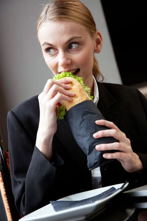 young businesswoman eating a sandwich photo