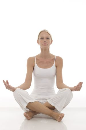 a young caucasian woman dressed in white sitting cross-legged doing yoga photo