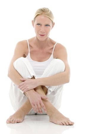 a young caucasian woman dressed in white sitting on the floor Stock Photo - 6826337
