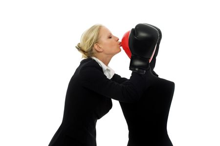 portrait of a young caucasian businesswoman with aggressive air wearing boxing gloves and kissing a dummy photo