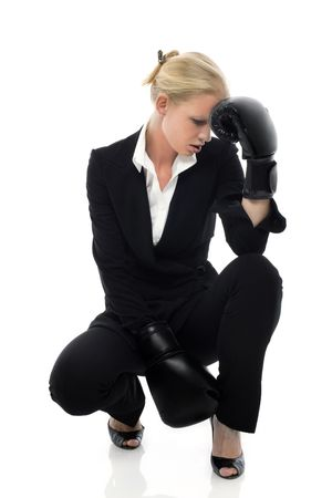 portrait of a young caucasian businesswoman tired with boxing gloves photo