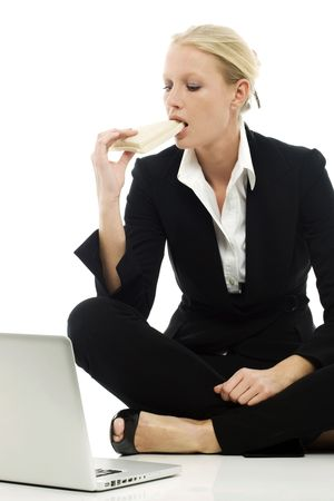 communications tools: portrait of a young caucasian businesswoman eating sitting on the floor with laptop