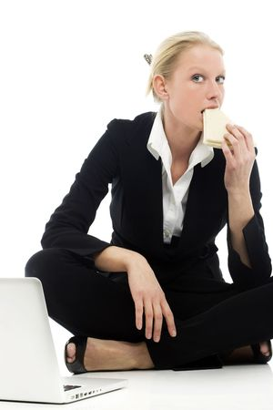 adult sandwich: portrait of a young caucasian businesswoman eating sitting on the floor with laptop