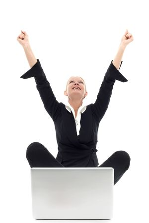 portrait of a young caucasian businesswoman sitting on the floor with arms up and laptop photo