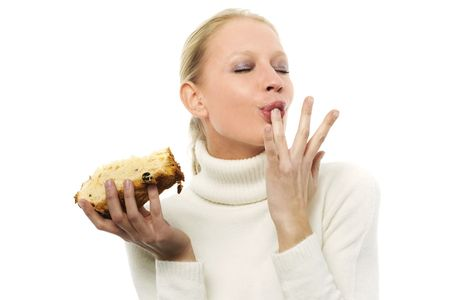sucking: portrait of a young caucasian woman wearing a white turtleneck sweater and holding a slice of panettone Stock Photo