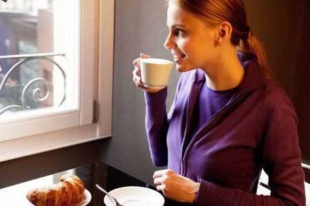 woman drinking cappuccino at breakfast and looking at the window photo