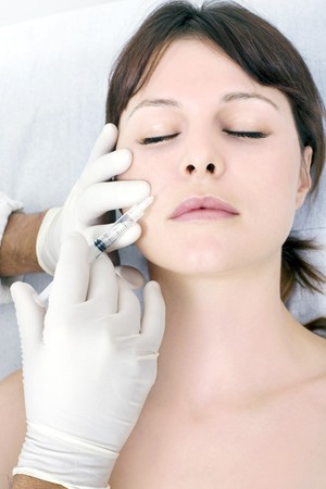 young caucasian woman receiving an injection of botox from a doctor photo