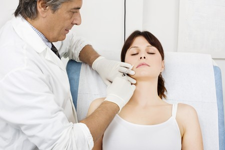 rejuvenated: young caucasian woman receiving an injection of botox from a doctor