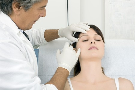 surgeon: young caucasian woman receiving an injection of botox from a doctor