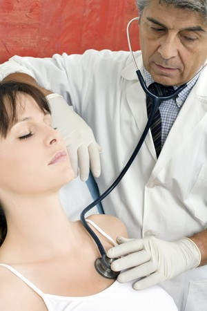 auscultate: man doctor visits a young caucasian woman with stethoscope