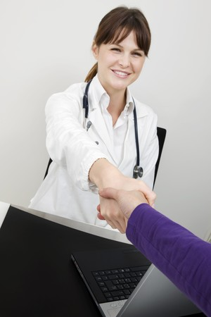 young caucasian woman doctor and patient shake hands photo