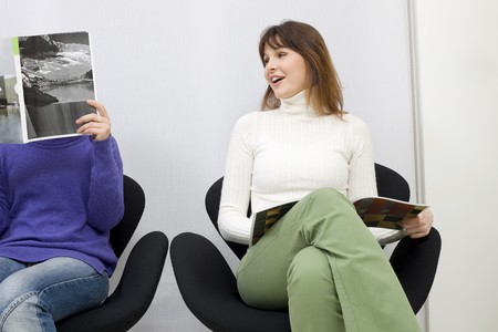 two women sitting in the waiting room for doctors photo