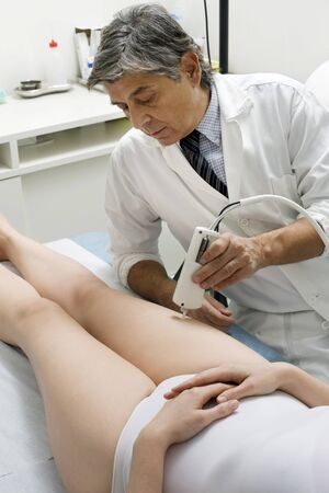 caucasian woman receiving laser treatment at the leg from a male doctor Stock Photo - 7031095