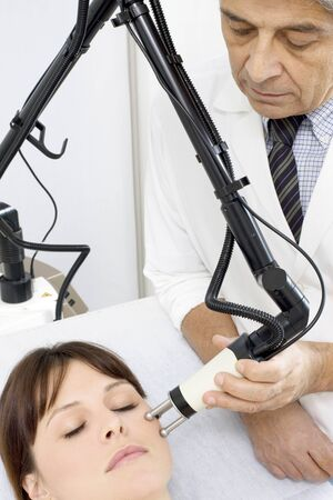 cosmetic surgery: young caucasian woman receiving electrostimulation lifting from a male doctor Stock Photo