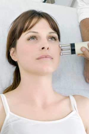 rejuvenated: portrait of a young caucasian woman receiving electrostimulation lifting